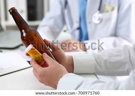 Alcoholic hold in hand empty bottle at doctor reception office closeup. Grief and despair, intoxicated, change life, drunkenness lifestyle, sobriety and temperance, bad habit dependence concept