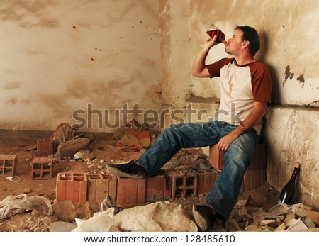 Alcoholic Man Drinking and Sitting against a filthy wall