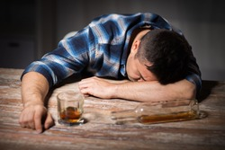 alcoholism, alcohol addiction and people concept - male alcoholic with glass of whiskey and bottle lying or sleeping on table at night