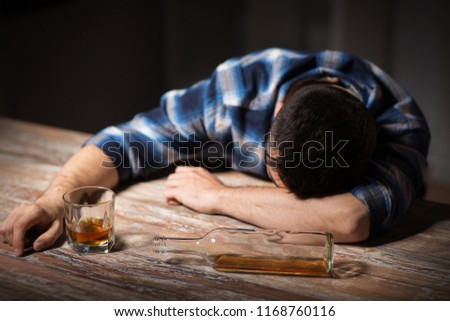 alcoholism, alcohol addiction and people concept - male alcoholic with glass of whiskey and bottle lying or sleeping on table at night #1168760116