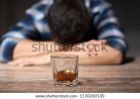 alcoholism, alcohol addiction and people concept - male alcoholic with glass of whiskey lying or sleeping on table at night
