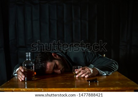 alcoholism, alcohol addiction and people concept - male alcoholic with glass of whiskey lying or sleeping on table at night #1477888421