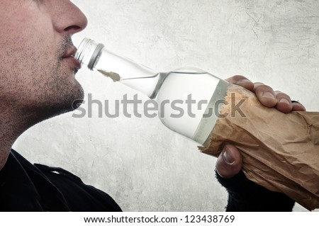 Alcoholism. Man drinking vodka from the bottle.