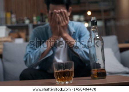 Alcoholism or Alcoholic concept : Close up young Asian guy feeling depressed drinking alcohol alone in pub or bar because life problem or stress. #1458484478