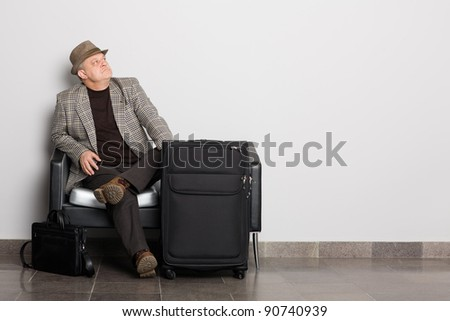 Alegant man waiting to board a airplane (train, ferry, bus). Waiting hall.