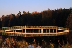 Alekseevskaya grove near Moscow is in the rays of the setting sun. Pedestrian Bridge beautifully reflected in the water of the pond.