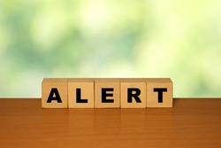 ALERT message word on a wooden desk on cube blocks with a green nature background