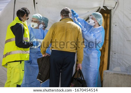 Alert pandemic Covid-19. Triage hospital field tent for the first AID, a mobile medical unit for patient infected with Corona Virus. Doctors with protective masks check the patiences at the entrance. Foto stock ©