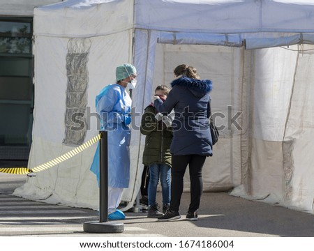 Alert pandemic Covid-19. Triage hospital field tent for the first AID, a mobile medical unit for patient infected with Corona Virus. Doctors with protective masks check a little girl at the entrance. Foto stock ©
