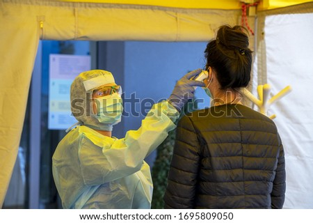 Alert pandemic Covid-19. Triage hospital field tent for the first AID, a mobile medical unit for patient infected with Corona Virus. Doctor with protective mask checks the patient's fever. Foto stock ©