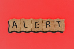 Alert, word in wooden alphabet letters isolated on red background