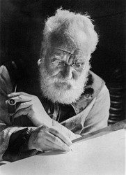 Alexander Graham Bell (1847-1922), writing at his desk in his study in Washington. 1913.