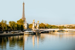 Alexandre bridge and Eiffel tower on Seine river during the morning light in Paris