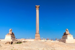 Alexandria, Egypt. Pompeys Pillar and ancient sphinxes. This Roman triumphal column was built in 297 AD
