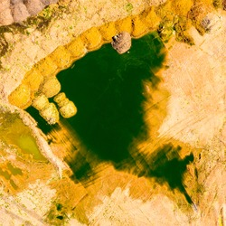 Algal blooms on lake in devastated landscape after mining. Environmental disaster from above. Ecology and industry theme.