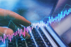 Algorithmic trading concept with virtual screen with growing stock market candlestick and circuit at laptop with hands background. Double exposure