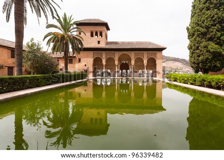Alhambra palace of Granada reflected in water showing palm trees