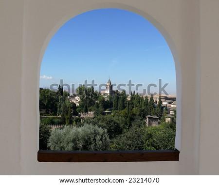 Alhambra through the arch window. In the center - Santa Maria church.