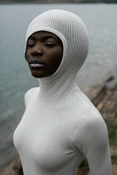 Alien. African beautiful model with perfect body in long tiny dress with hood. Muscles, chocolate skin. Water on background, natural colors. Summer landscape. Calm and balance