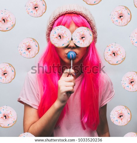 alien girl with donuts for eyes and the beanie hat is sucking candy