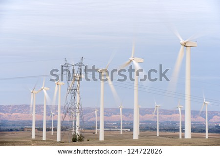 aligned windmills for renowable electric production and power line, Pozuelo de Aragon, Zaragoza, Aragon, Spain - stock photo