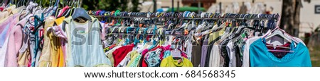 alignment of second hand baby and children clothing displayed on rack per size at outdoor flea market for sale, exchange, recycle, donate and reuse against over-consumption shopping