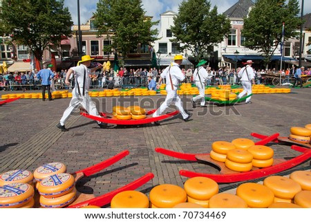 ALKMAAR, HOLLAND, THE NETHERLANDS - SEPTEMBER 3: Cheese workers walking to a lorry. This traditional market is held a few Fridays during Summer. September 3, 2010 in Alkmaar, Holland, The netherlands - stock photo