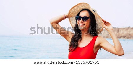 All charm and sunshine. Chic girl in front of light blue sea water is wearing bright swimsuit, taupe round hat and cat-shaped black sunglasses and welcoming the morning sun. #1336781951