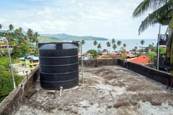 All city roofs are occupied by black water storage tanks and different satellites. Water tank on the roof in Asia. Water heating tank against sea and the city. Asian water supply and heating system