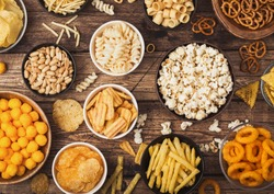 All classic potato snacks with peanuts, popcorn and onion rings and salted pretzels in bowl plates on wood. Twirls with sticks and potato chips and crisps with nachos and cheese balls. Top view