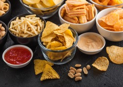 All classic potato snacks with peanuts, popcorn and onion rings and salted pretzels in bowl plates on black table. Twirls with sticks and potato chips and crisps with nachos and cheese balls.