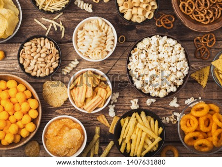 All classic potato snacks with peanuts, popcorn and onion rings and salted pretzels in bowl plates on wood. Twirls with sticks and potato chips and crisps with nachos and cheese balls. Top view Foto stock ©