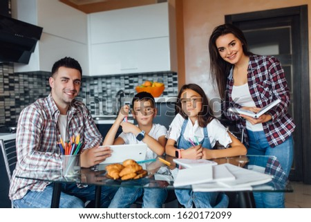 All family  doing homework for school, while sitting at kitchen table at home, togetherness time at modern house.