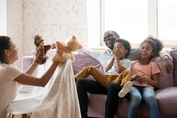 All family enjoy leisure funny educational activity on weekend at home concept. African mother holds hand puppet marionette stuffed animal toys showing theatrical performance for children and husband
