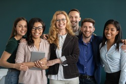 All for one. Group portrait of happy ambitious motivated multiethnic business partners specialists team workforce of diverse gender and age standing close together hugging smiling looking at camera