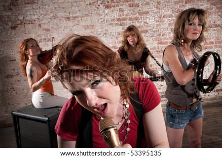 All-girl band performing in stylish clothing at a warehouse