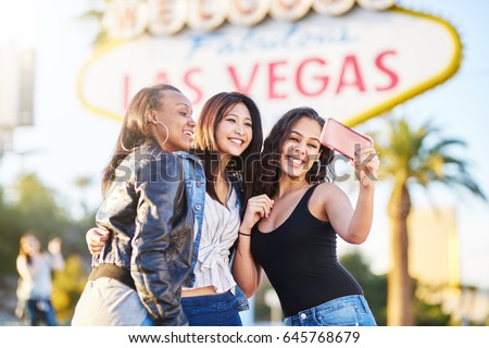 all girl group of friends having fun taking selfies in front of welcome to las vegas sign