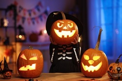 All hallows eve. Little girl child in witch hat and skeleton costume holding glowing jack o lantern carved pumpkin in front of her face, standing behind table with Halloween decorations in dark room