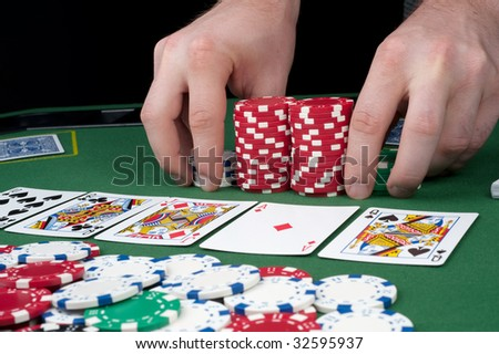 All in motion with five cards face up in front of a pot of chips
