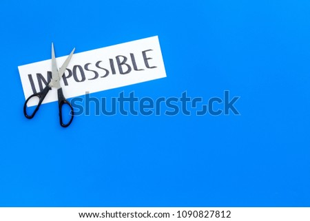 All is possible concept. Cutting the part im of written word impossible by sciccors. Blue background top view copy space #1090827812