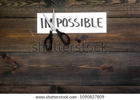 All is possible concept. Cutting the part im of written word impossible by sciccors. Dark wooden background top view copy space #1090827809