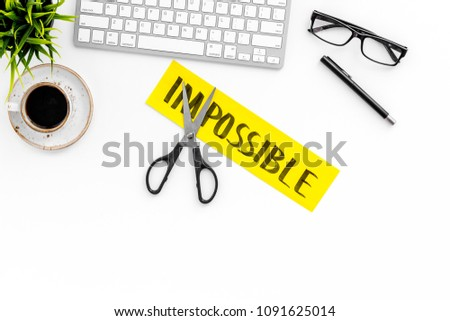 All is possible concept. Cutting the part im of written word impossible by sciccors. Office desk. White background top view copy space #1091625014