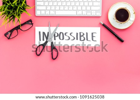 All is possible concept. Cutting the part im of written word impossible by sciccors. Office desk. Pink background top view copy space #1091625038