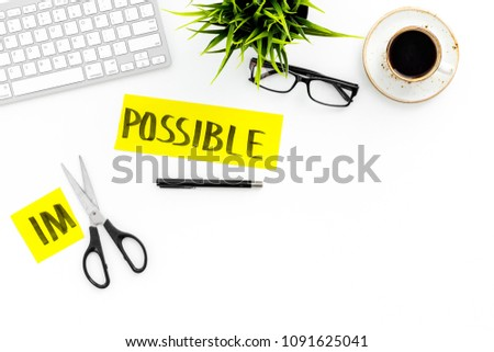 All is possible concept. Cutting the part im of written word impossible by sciccors. Office desk. White background top view copy space #1091625041