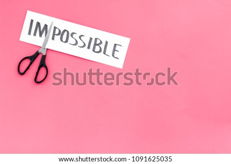 All is possible concept. Cutting the part im of written word impossible by sciccors. Pink background top view copy space #1091625035