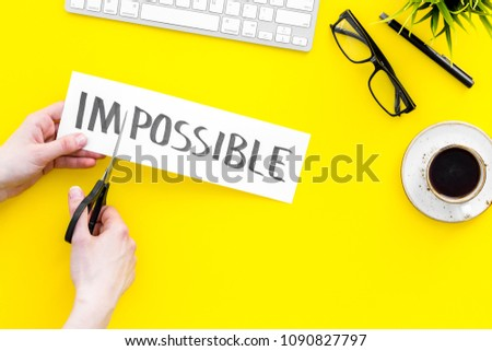 All is possible concept. Cutting the part im of written word impossible by sciccors. Yellow background top view copy space #1090827797
