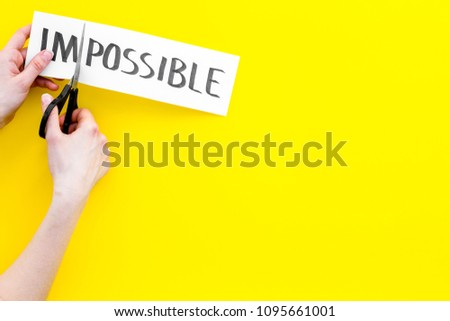 All is possible concept. Hands cutting the part im of written word impossible by sciccors. Yellow background top view copy space #1095661001