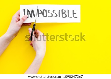 All is possible concept. Hands cutting the part im of written word impossible by sciccors. Yellow background top view copy space #1098247367