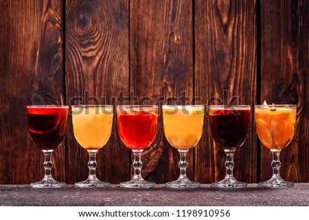 all kinds mulled wine. Variety of mulled wine in beautiful glasses standing in a row on a dark wooden background. advertising photo of mulled wine. Close up #1198910956