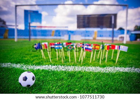 All nations flag on football pitch. Green grass. Football net and blue sky in background #1077511730